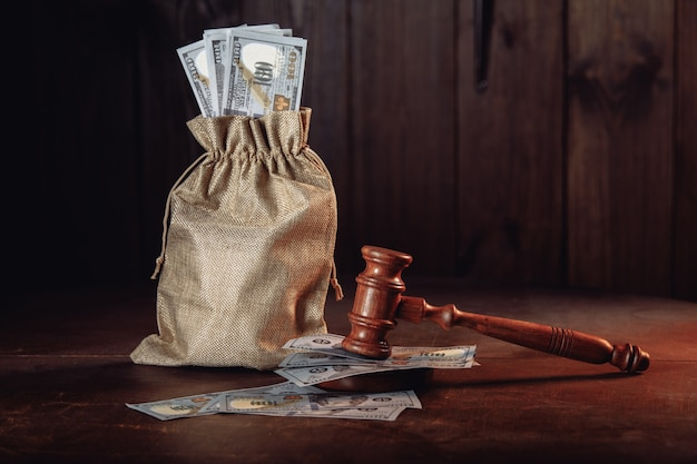 Money bag with dollar banknotes and judges gavel litigation dispute resolution conflict of interest settlement
