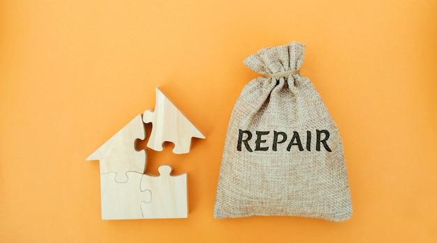 Денежный мешок с надписью ремонт и деревянный дом концепция разрушенного дома