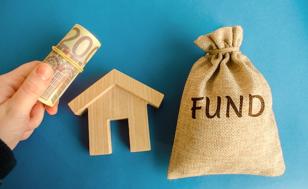 Money bag with the word fund wooden house and euro bills in hand real estate investment concept