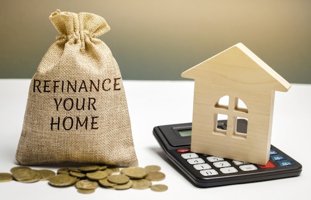 Money bag with the words refinance your home and miniature house.