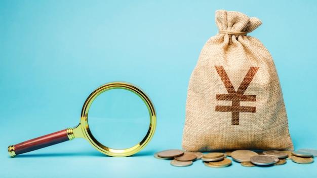 Денежный мешок со знаком иены или юаня и увеличительным стеклом.