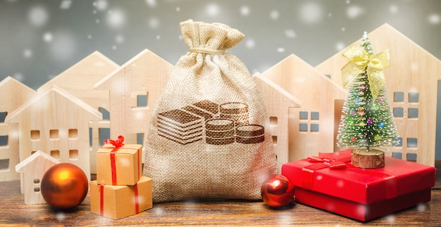 Money bag, wooden houses, christmas tree and gifts.