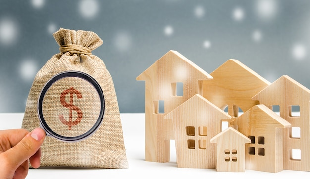 Money bag and a wooden houses with snow. ual image real estate market in the winter season