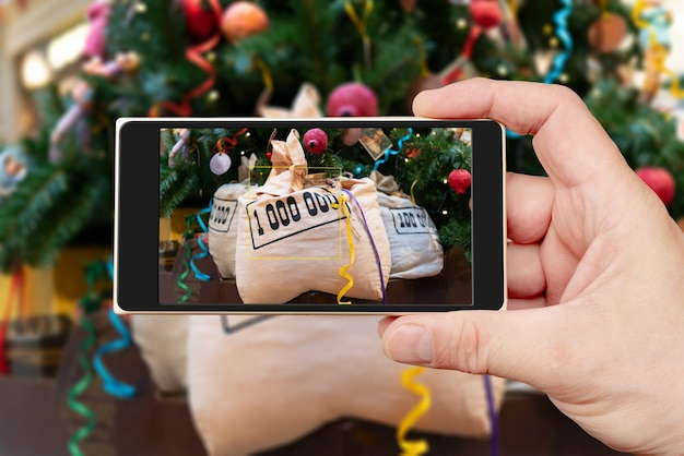 Money bags under the christmas tree on the smartphone screen.