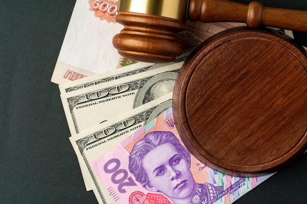 Деньги купюры с молотком судьи. концепция коррупции с валютой российских рублей, украинских гривен и американских долларов