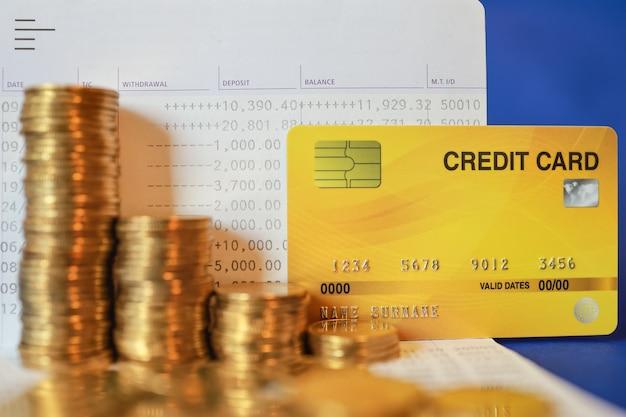 Деньги бизнес и концепция экономии. крупный план поддельной кредитной карты макета с стопкой монет на банковской сберегательной книжке на синем фоне.