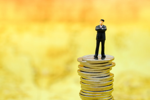 Money, business and risk concept. businessman miniature figure standing on top of unsteady stack of silver coins.