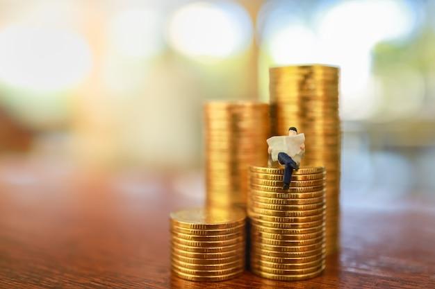 Концепция денег, бизнеса, сбережений и планирования. закройте вверх диаграммы perople бизнесмена миниатюрной сидя и читая газету на стоге золотых монеток на деревянном столе с космосом экземпляра.
