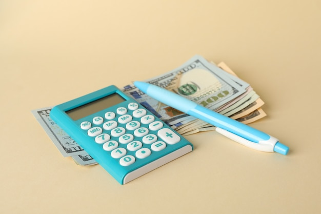 お金、電卓、ペン、ベージュの表面