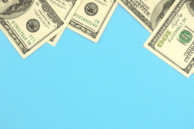 Money cash dollar frame composition, office desktop blue color background with copy space, top view photo