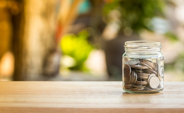 Money coin in glass jar for savings and financial investment concept