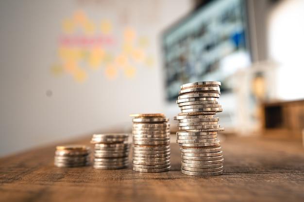 돈 동전 성장 비즈니스 및 컴퓨터 개념, 실버 동전 나무 책상에 쌓인