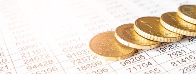Монета денег на листе бухгалтерского отчета, экономия денег или финансовой концепции.