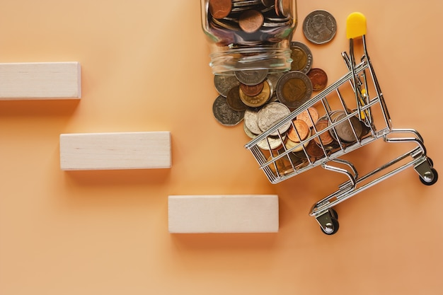 Money and coins form glass jar to mini shopping cart or trolley with wooden toy staircase