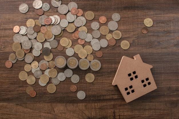 木製のテーブル、住宅ローン、不動産のコンセプトで木製の家のモデルで成長するお金のコイン