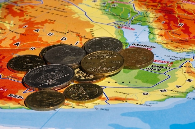 Money, coins of ringgit malaysia, singapore dollar and saudi arabia riyals on the map of saudi arabia, selected focus. business, finance, economy and investment concept