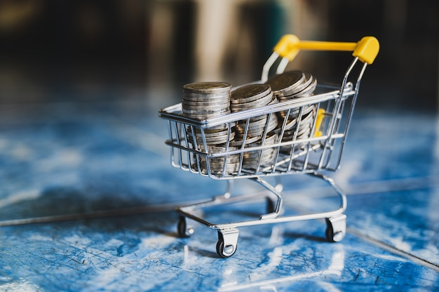 Money coins in yellow shopping cart blur abstract background.