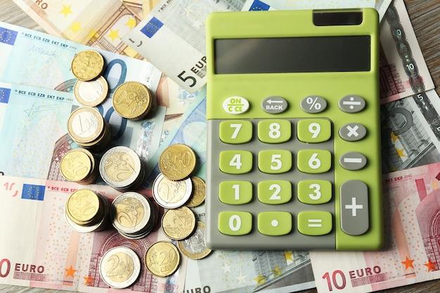 お金の概念。紙幣と硬貨の緑の計算機、クローズアップ