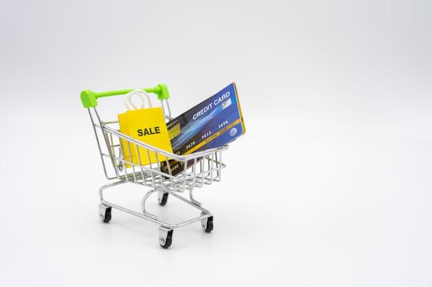 Концепция денег кредитных карточек в магазинной тележкае на предпосылке белизны изолята.