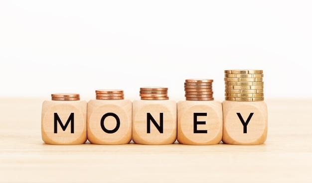 お金の概念。木製のテーブルにテキストお金とコインが付いた木製のブロック。