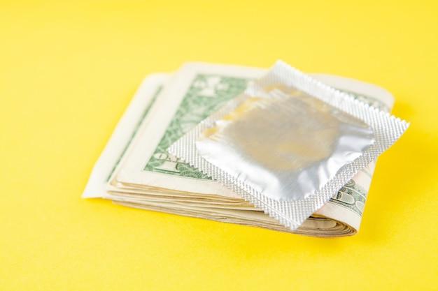 Money condom on yellow scene