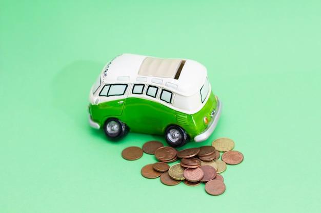 ピンクの貯金箱に落ちるお金の通貨、緑に分離