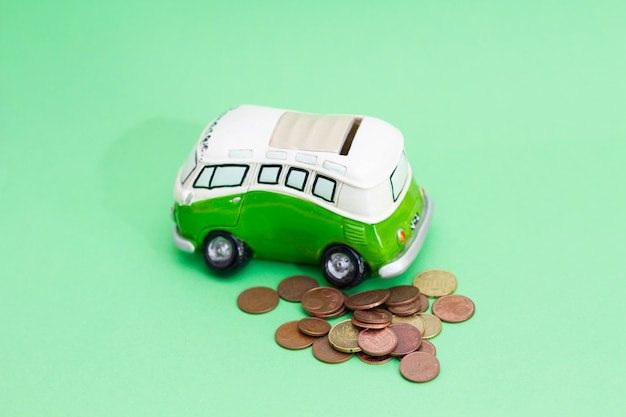 Money currency falling into a pink piggy bank, isolated on green