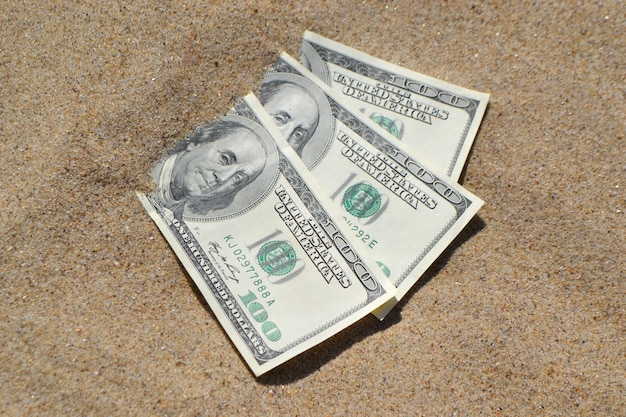 Money dolars half covered with sand lie on beach close-up.
