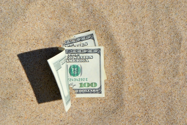Money dolars half covered with sand lie on beach close-up