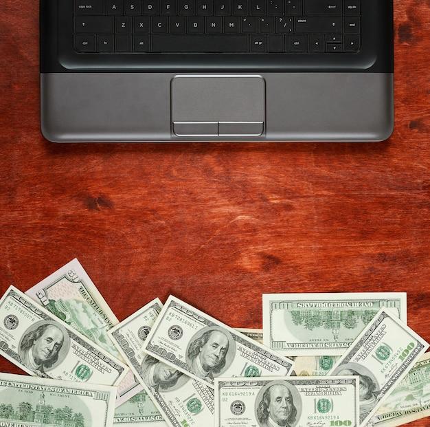 木の背景にお金のドル通貨とラップトップ