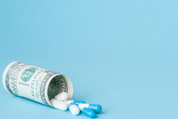Деньги доллар, свернутые с потекающими таблетками, изолированными на синей стене