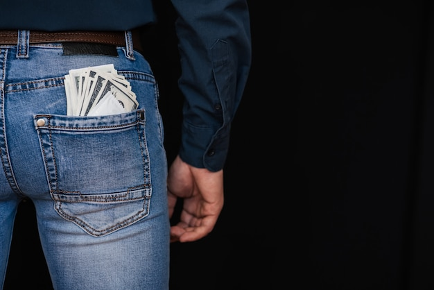 Money dollars and a condom in the back pocket of men's jeans