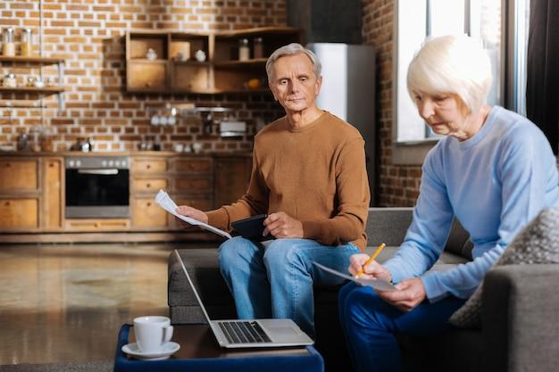 돈 비용. 함께 앉아서 예산을 계획하는 동안 몇 가지 계산을하는 멋진 즐거운 노인 부부