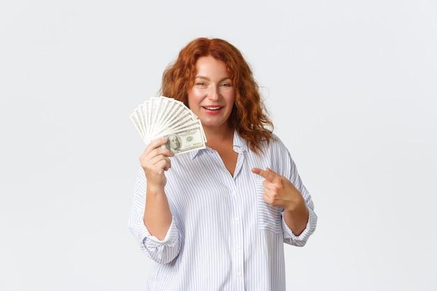 Деньги, финансы и люди концепции. нахальная богатая женщина средних лет с рыжими волосами показывает большую сумму денег, держит огромную сумму наличными и указывает на нее, выигрывает приз, белый фон