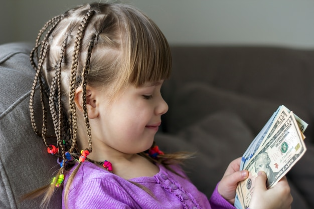 Концепция денег, финансов и людей - усмехаясь маленькая девочка с долларом получает деньги наличными.