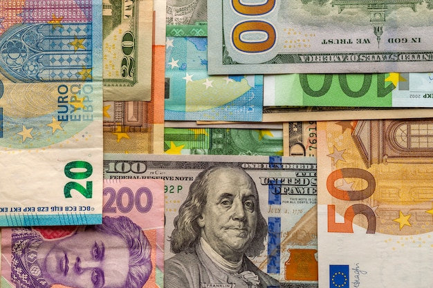 Money and finances concept. one hundred dollar new bill on colorful abstract background of ukrainian, american and euro national currency banknotes.