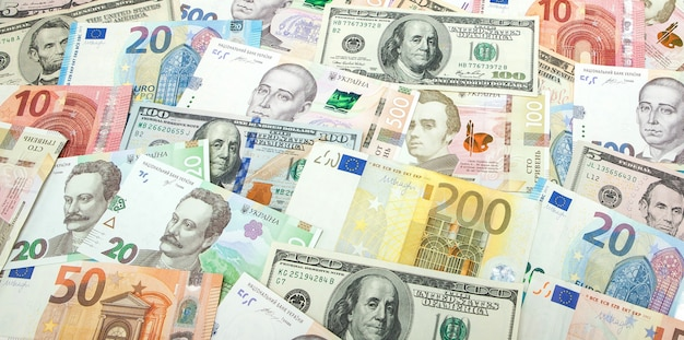 Money and finances concept. one hundred dollar new bill on colorful abstract background of ukrainian, american and euro national currency banknotes