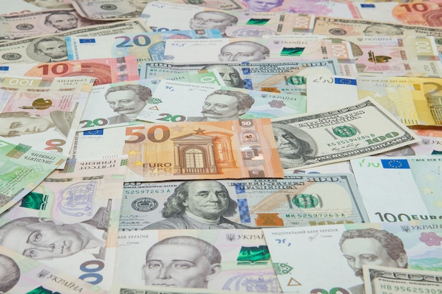 Money and finances . one hundred dollar new bill on colorful abstract  of ukrainian, american and euro national currency banknotes