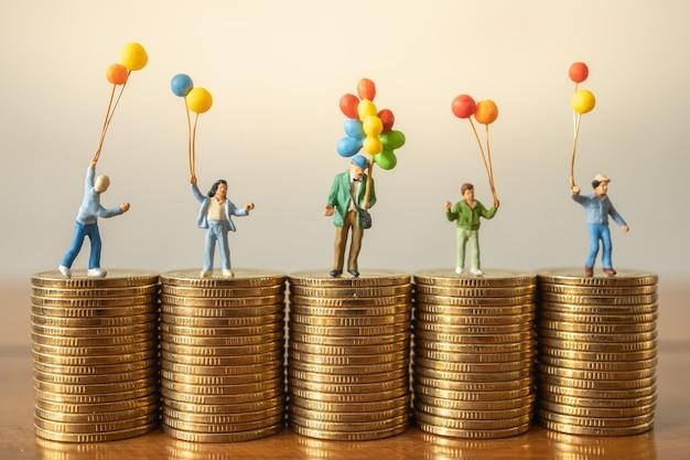 お金の財政および家族の概念。木製のテーブルの上の金貨のスタックに立って遊んでいる子供たちとバルーン売り手のミニチュアフィギュアの人々のグループ。