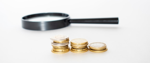 Money financial business growth concept stack of coins with magnifying glass