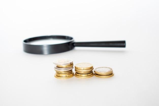 돈 금융 비즈니스 성장 개념 돋보기와 동전의 스택
