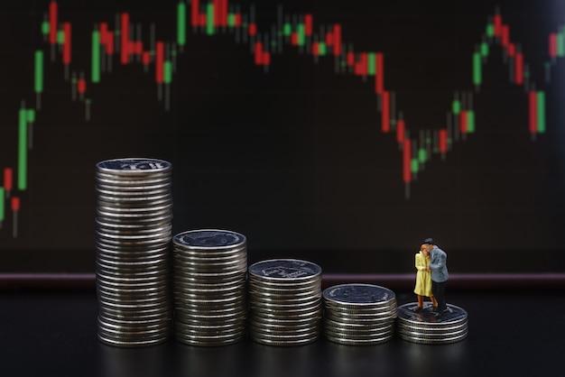 돈, 금융, 비즈니스 투자 및 가족 개념입니다. 부모와 자식 미니어처 피규어는 촛대 차트를 배경으로 동전 더미를 걷고 함께 포옹하고 키스합니다.