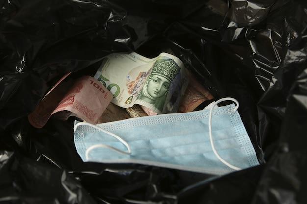 Soldi da tutto il mondo e una maschera per il viso dentro un sacco della spazzatura di plastica nera.