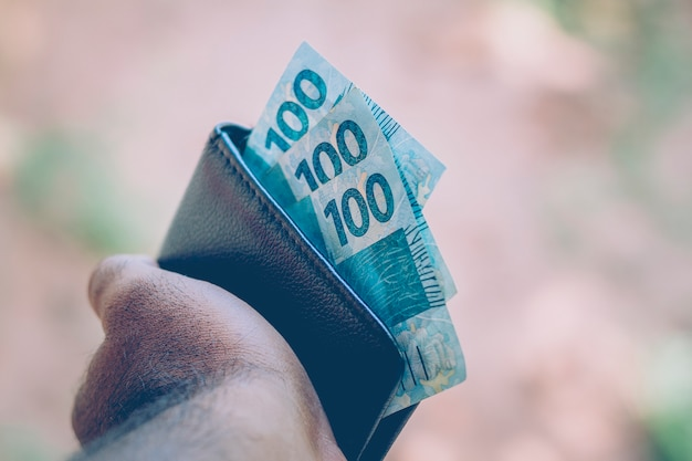 Деньги из бразилии. реальные ноты, бразильская валюта внутри черного кошелька. понятие финансов, экономики и богатства.