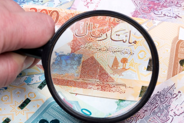 Money from qatar in a magnifying glass a business background