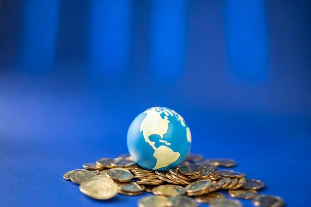 돈 글로벌 비즈니스 개념입니다. 파란색 배경에 더미와 금화에 미니 세계 공의 근접 촬영.
