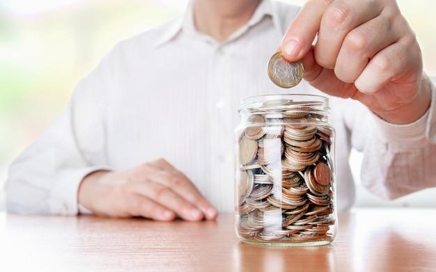 ガラスの瓶の中のお金。手はコインを開発に置きます。投資コンセプト。経済成長。ビジネス管理。資本の蓄積。