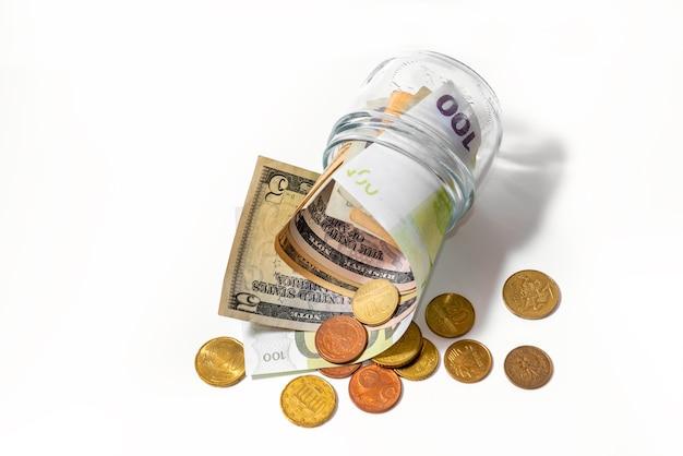 흰색 배경에 유리 항아리에 돈. 경제의 개념.