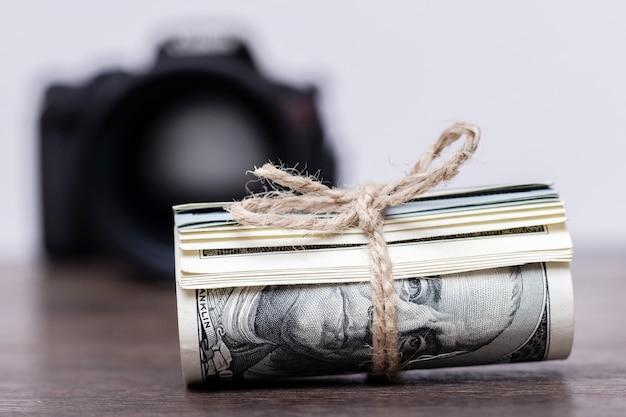 Деньги в рулоне связаны веревкой возле камеры. заработок фотографа