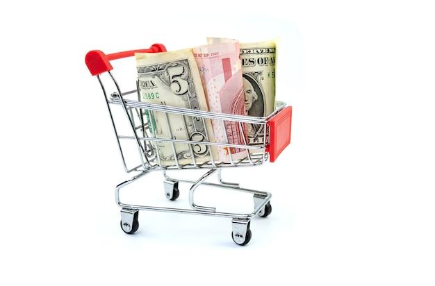 白い背景の上のトロリーのお金。ショッピング費用、スーパーマーケット、金融、お金の概念。